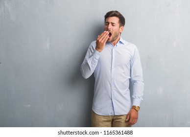 Handsome young business man over grey grunge wall wearing elegant shirt bored yawning tired covering mouth with hand. Restless and sleepiness.