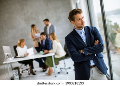 Handsome young business man standing confident in the office in front of his team