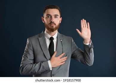 Handsome young business man taking an oath wearing a grey jacket