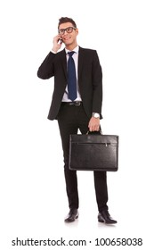 handsome young business man talking on a  mobile phone and holding a suitcase on white background