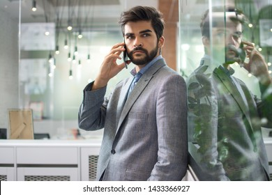 Handsome young business man talking on mobile phone in office
