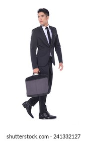 handsome young business man walking carrying a suitcase �full body