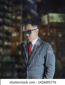 Handsome young business man wearing suit, red tie, and sunglasses, standing inside an office building behind the glass window with the city light reflection.