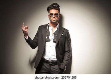 Handsome young business man wearing sunglasses holding one finger up.