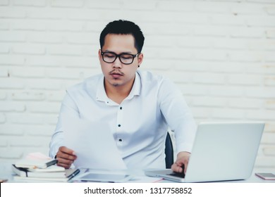 Handsome young business man with working place in creative office