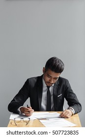 Handsome young business man writing, businessman working with documents sign up contract, sitting at the desk at office, wear elegant suit and tie isolated over grey background