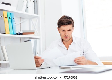 Handsome young businessman analyzing documents and laptop in office
