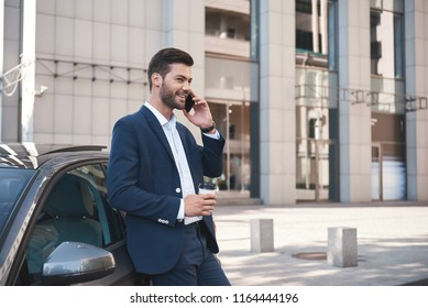 Handsome young businessman in a big city, talking on the phone and drinking coffee