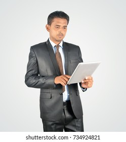 Handsome young businessman browsing on tablet pc, isolated very professionally