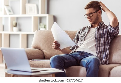 Handsome young businessman in casual clothes and glasses is studying documents, scratching his head and smiling while working at home