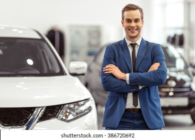 Handsome young businessman in classic blue suit is smiling and looking at camera while standing near the car in a motor show