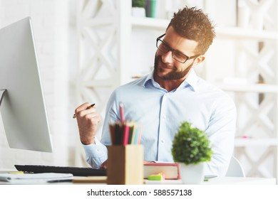 Handsome young businessman with clinched fist and excited face expression sitting at his office desk and looking at computer screen. Success concept