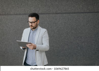 Handsome young businessman with digital tablet by the grey wall
