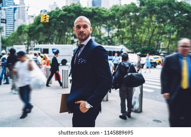 Handsome young businessman dressed in elegant expensive suit looking away while walking in urban setting of downtown.Successful entrepreneur in formal wear with folder in hand strolling on street