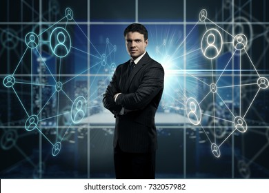 Handsome young businessman with folded arms standing in blurry office interior with glowing HR holograms. Innovation concept. Double exposure