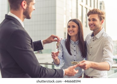Handsome young businessman is giving keys to happy smiling young couple. Young man is giving money. Modern buildings in the background