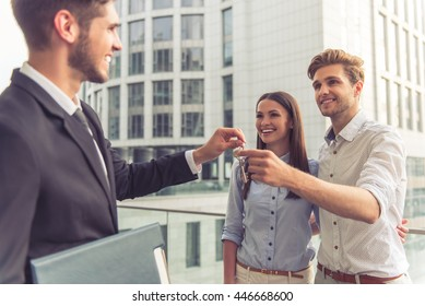 Handsome young businessman is giving keys to happy smiling young couple, modern buildings in the background