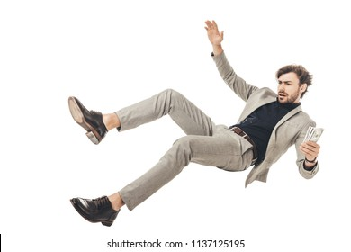 handsome young businessman holding cash in hand and falling isolated on white