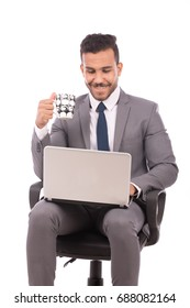 Handsome young businessman holding a cup of coffee and using the laptop, guy wearing gray suit, isolated on white background
