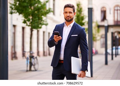 A handsome young businessman holding his laptop while using his phone and standing on the street