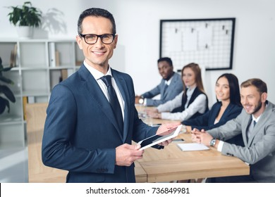 handsome young businessman holding tablet in conference hall with partners sitting at table