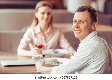 Handsome young businessman is looking at camera and smiling during business lunch at the restaurant, woman in the background