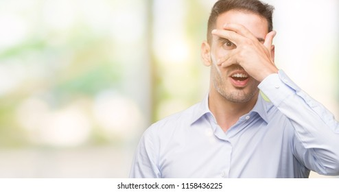 Handsome young businessman peeking in shock covering face and eyes with hand, looking through fingers with embarrassed expression.