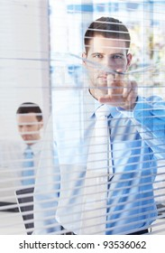 Handsome young businessman peeping through blind from bright office.?