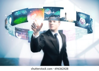 Handsome young businessman pointing at abstract colorful social media swirl in blurry interior. Multimedia concept