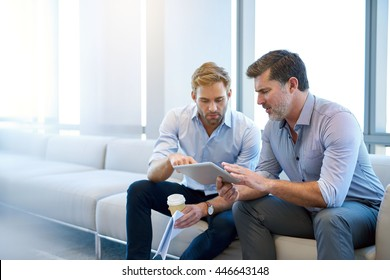 Handsome young businessman pointing something out to his mature corporate manager on a digital tablet while sitting in a modern business lounge