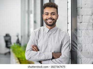 Handsome young businessman portrait. Cheerful self confident smiling man with crossed hands office. Business, success, people concept