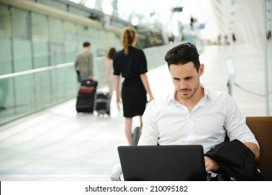 handsome young businessman in public station working on computer in wifi area while waiting for his aircraft or train