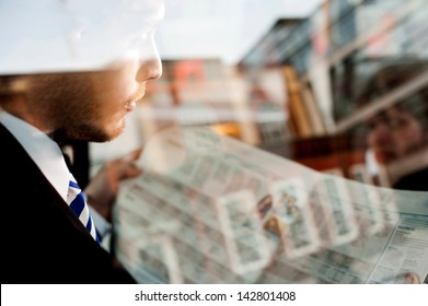 Handsome young businessman reading newspaper inside taxi cab.
