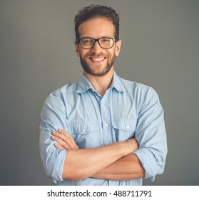 Handsome young businessman in shirt and eyeglasses is looking at camera and smiling while standing with crossed arms on gray background