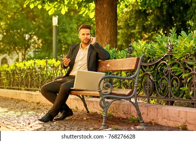 A handsome young businessman siting on a bench with his laptop on a sunny street next to a park while talking on his phone