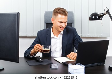 Handsome young businessman sitting in his office drinking his coffee