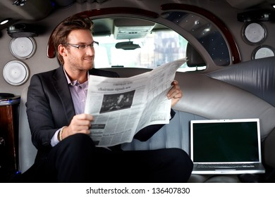 Handsome young businessman sitting in limousine, reading newspaper, smiling.