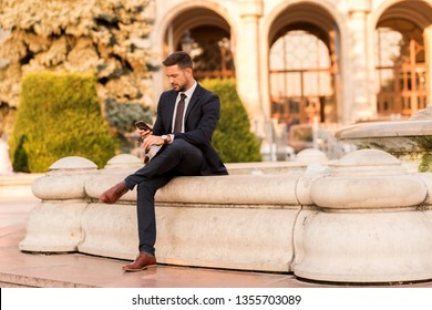 A handsome young businessman sitting next to a fountain and using his smartphone on a sunny day.