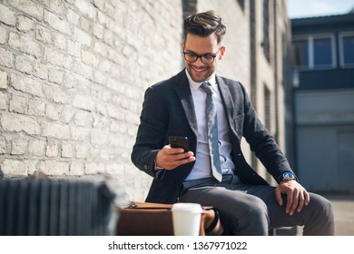 Handsome young businessman sitting on bench and checking his smart phone
