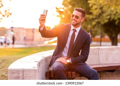 A handsome young businessman sitting on a bench and taking a selfie on a sunny day.