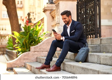 A handsome young businessman sitting on the stairs and using his smartphone at the Basilica in Budapest Hungary.