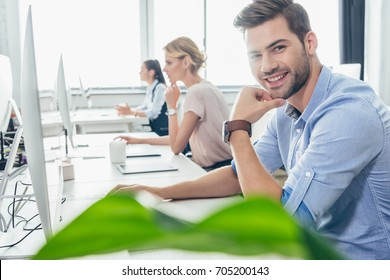 handsome young businessman smiling at camera while working with colleagues in office
