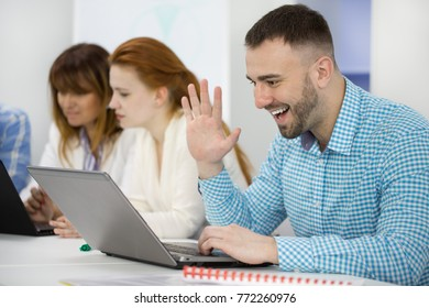 Handsome young businessman smiling cheerfully waving at someone while having vide conference on his laptop office corporate business communication connectivity interaction concept