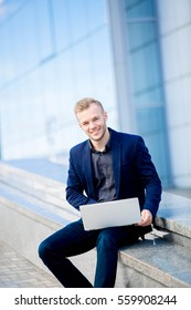 handsome young businessman smiling and looking right, holds the computer on a background of glass building