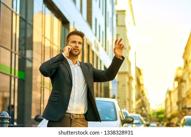 A handsome young businessman standing in front of the office building, talking on his phone and waving for a taxi with his hand