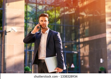 A handsome young businessman standing in front of the office building with his laptop in his hand while talking on his phone