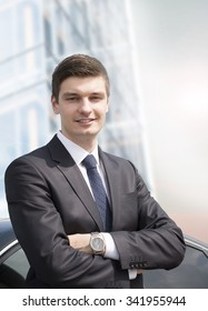 Handsome young businessman standing near his car