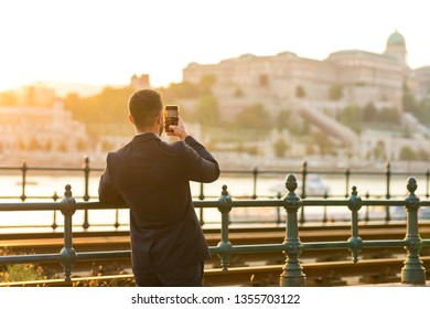 A handsome young businessman standing next to a tramline and taking a photo with his smartphone on a sunny day.