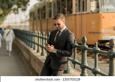 A handsome young businessman standing next to a tramline and using his smartphone on a sunny day.