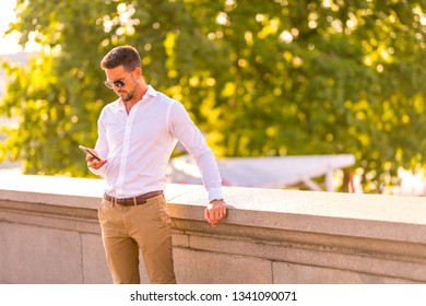 A handsome young businessman standing on the bridge and using his smartphone on a sunny day.